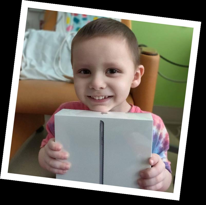 Boy holding iPad in room