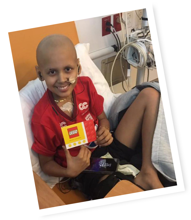 Boy in hospital bed holding a Lego card